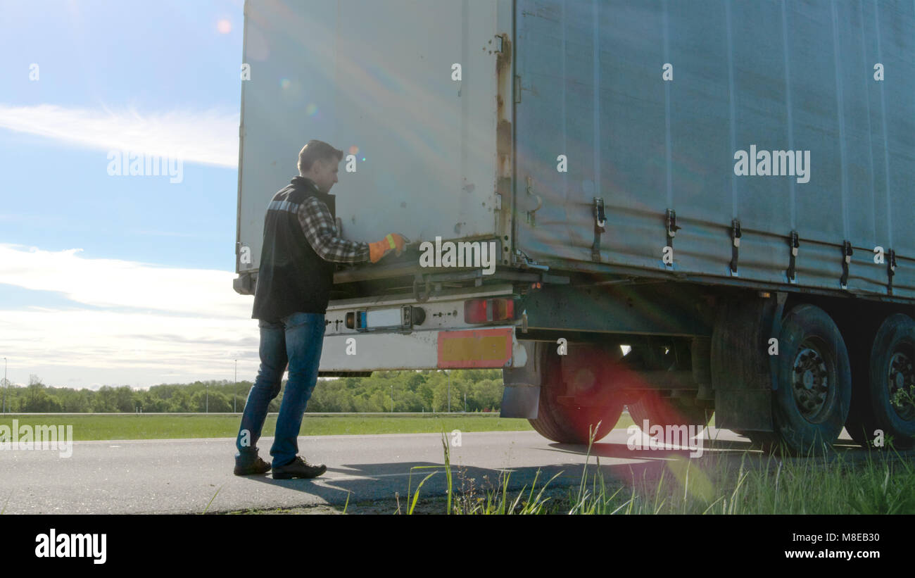 Truck Driver Closes Doors of His Parked  Truck Cargo Trailer. Professional Driver Wears Heavy Duty Gloves. - Stock Image
