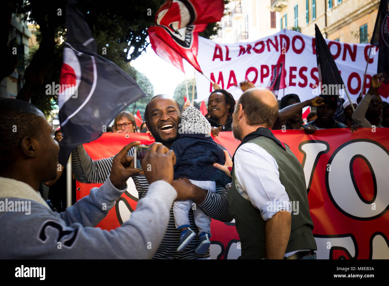 Savona, Italy - October 15, 2017: Young African father with daughter in arms during an anti-fascist parade organized - Stock Image