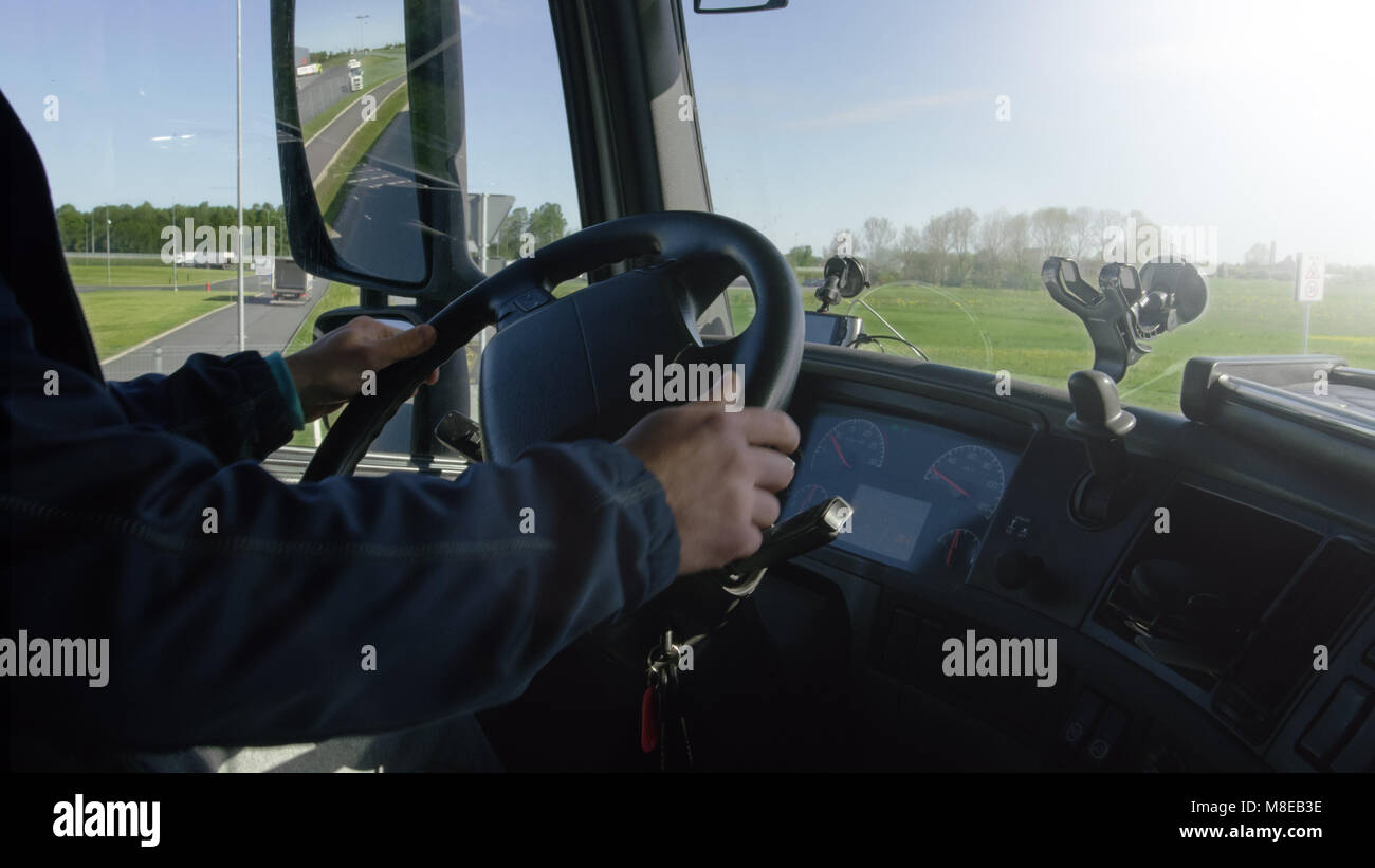 Inside of Cabin View of the Professional Truck Driver Driving His Big  Vehicle on the Road. Industrial Warehouses - Stock Image