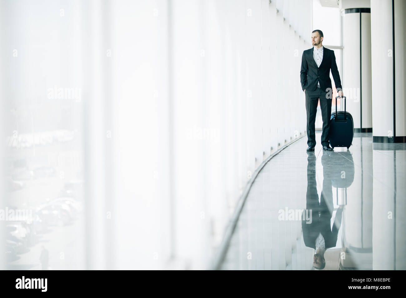 Business man at international airport moving to terminal gate for airplane travel trip. - Stock Image