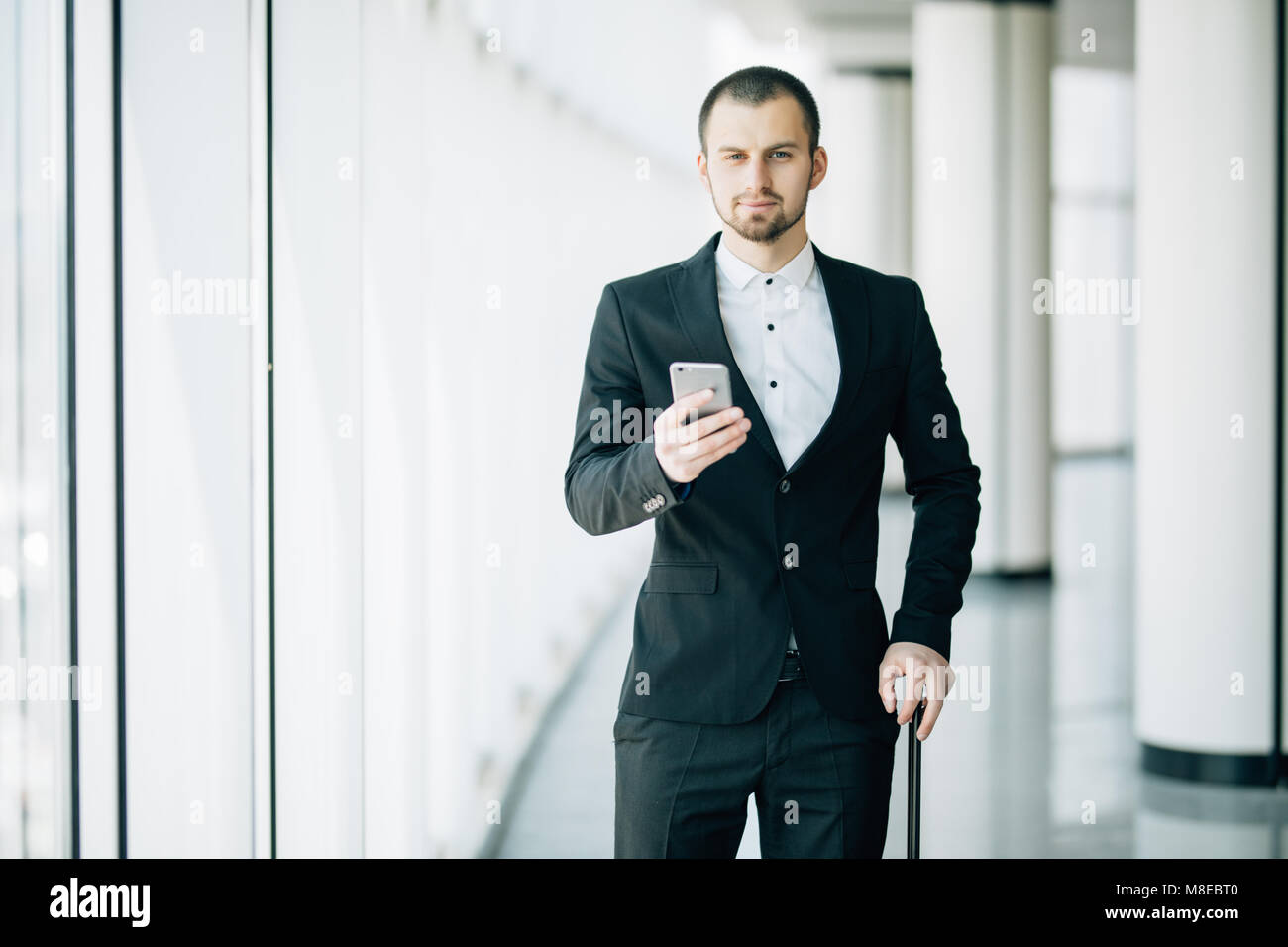 Happy young businessman walking and looking at mobile phone at airport. Handsome business executive texting on smartphone - Stock Image