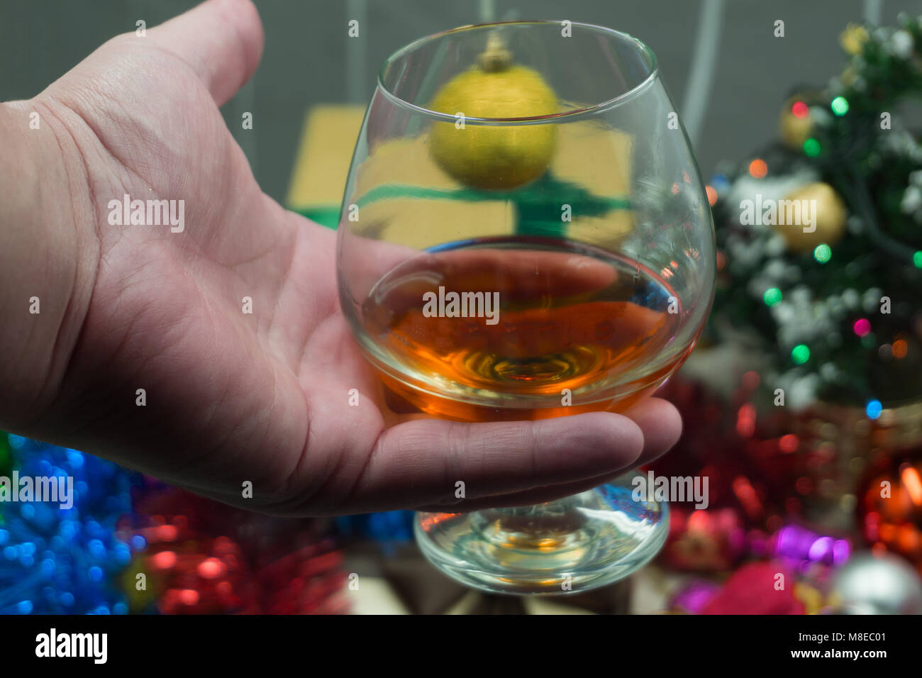 man with a glass of whiskey and all the glitters . Stock Photo