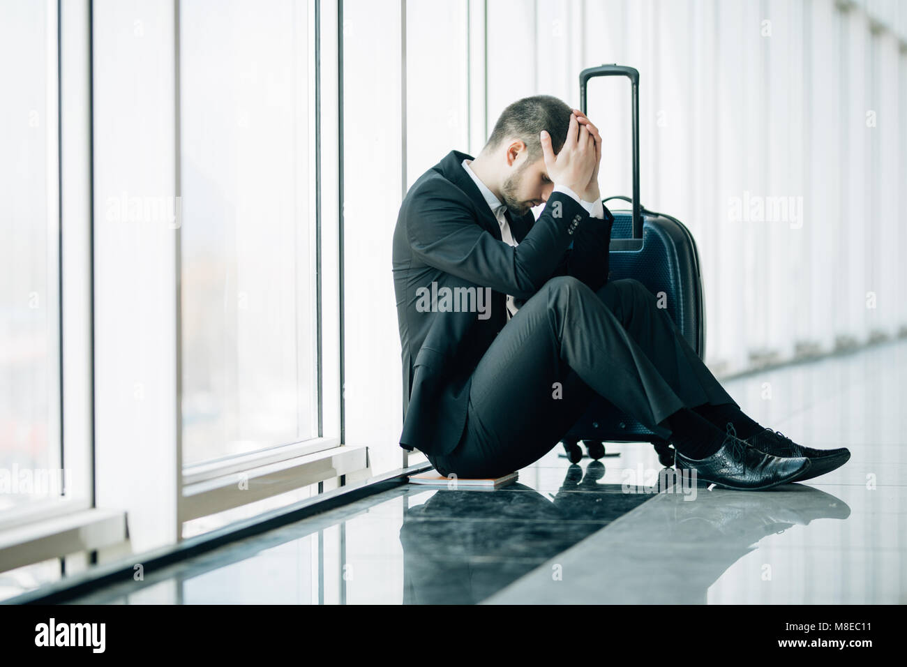 Serious businessman worrying something, sitting and touch his head at the airport terminal. Businessman miss his - Stock Image