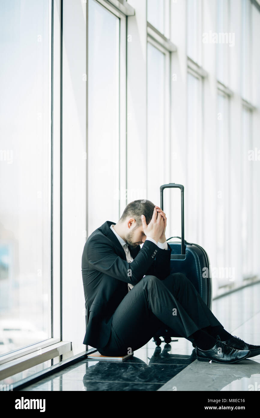 Business man sitting at the terminal airport on the floor with suitcase flight delay, two hands touch at head, headache, - Stock Image