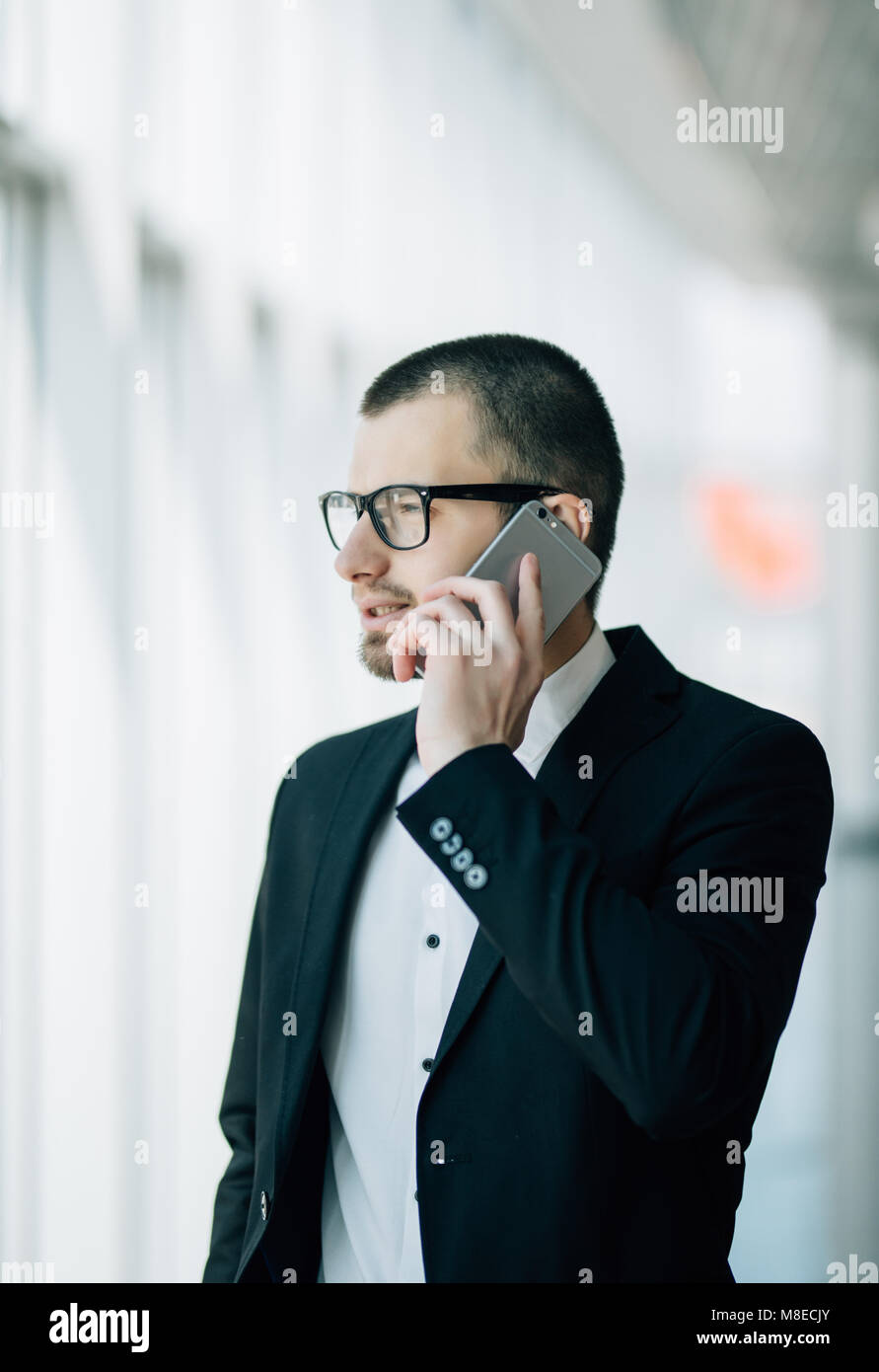 Mature business man standing inside office building and using cell phone. Man standing by window and talking on - Stock Image