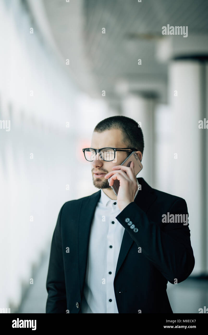 Businessman talk to cellphone and look out of window - Stock Image