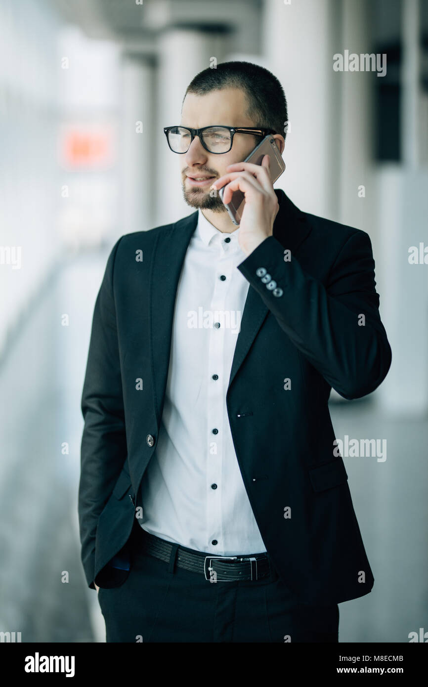 Handsome business CEO with designer stubble, talking confidently on his mobile phone while looking out of large - Stock Image