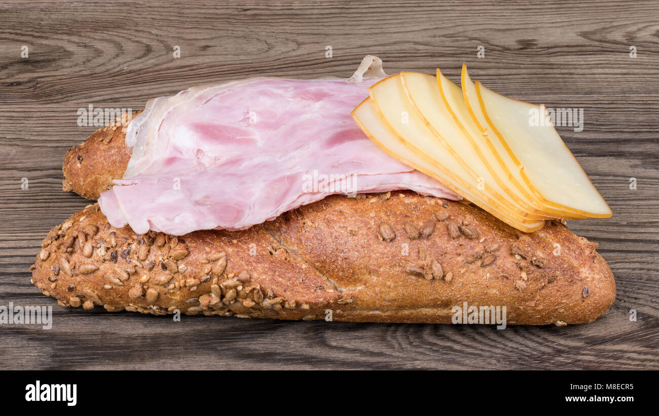 Two long bread rolls with slices of ham hock and hard cheese. Crunchy whole grain baguettes with sliced ham and - Stock Image