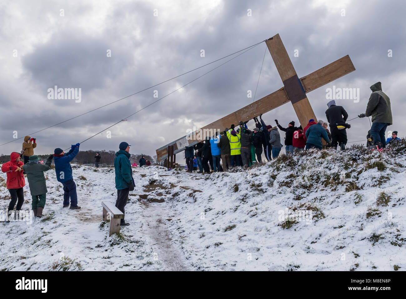 Otley Chevin, UK, 17th March 2018. On a cold, snowy morning, volunteers from the local churches, using ropes, raise - Stock Image