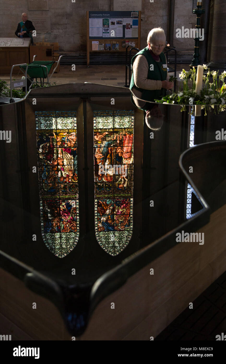 A woman arranges flowers at Salisbury Cathedral in Salisbury, Wiltshire, England. A stained glass window reflects Stock Photo