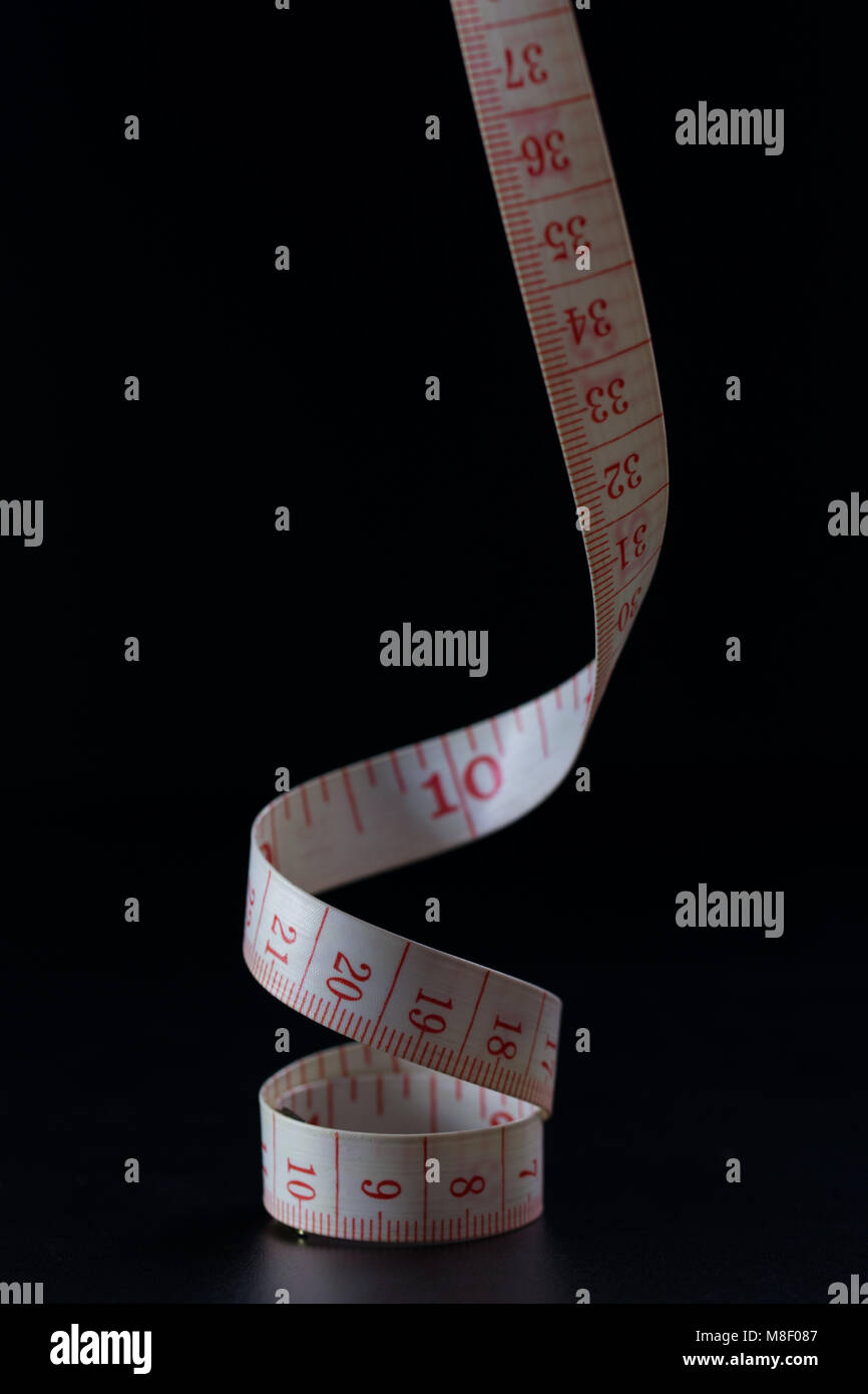 Coiled Tailors tape measure showing centimetres and Inches close up black background - Stock Image