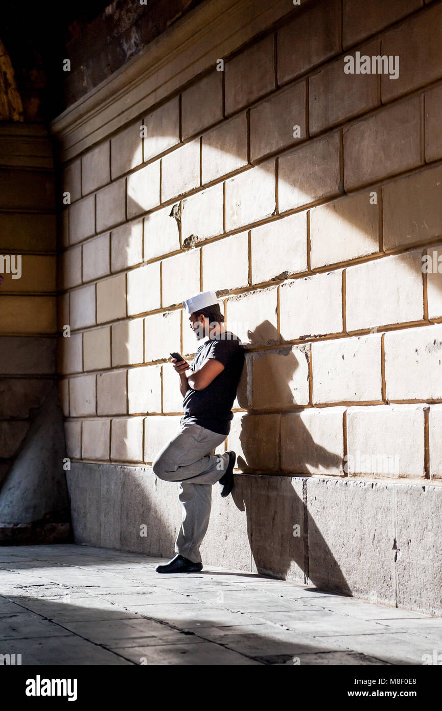 A chef takes a break from the kitchen to check his phone in an alley way by the beach walk in Nice, France. Stock Photo