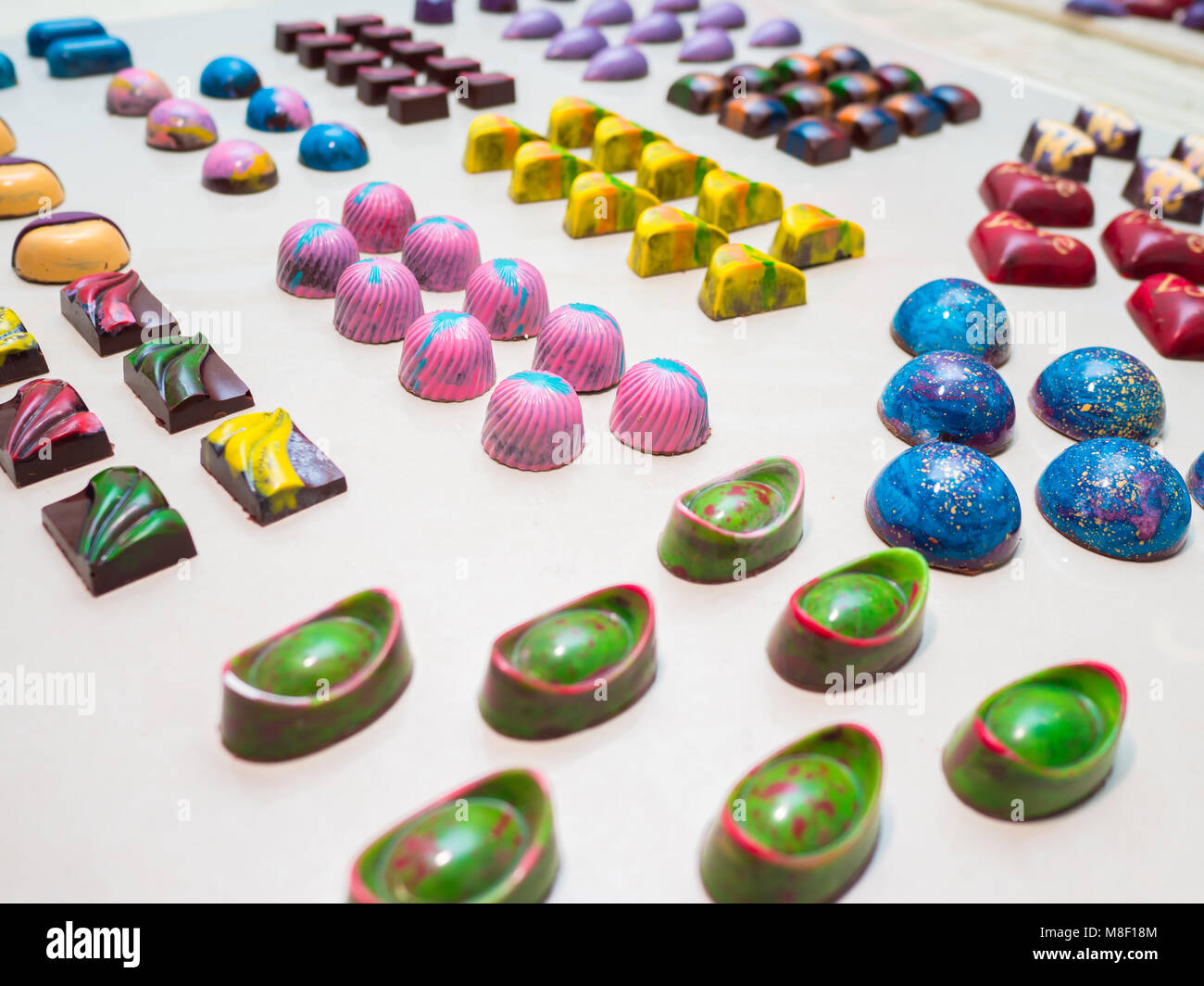 Assortment of luxury handmade chocolate candy collection isolated on white background. Set of colorful chocolate - Stock Image