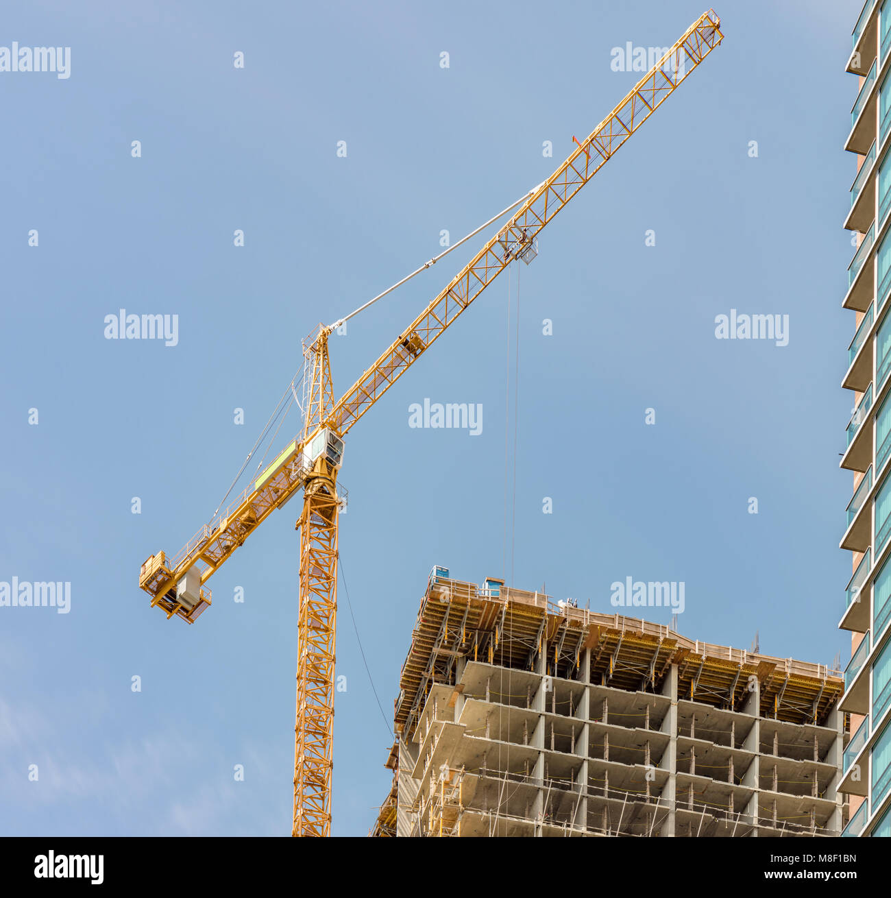 new building, construction of a modern multi-story building with a tower crane and other construction equipment - Stock Image