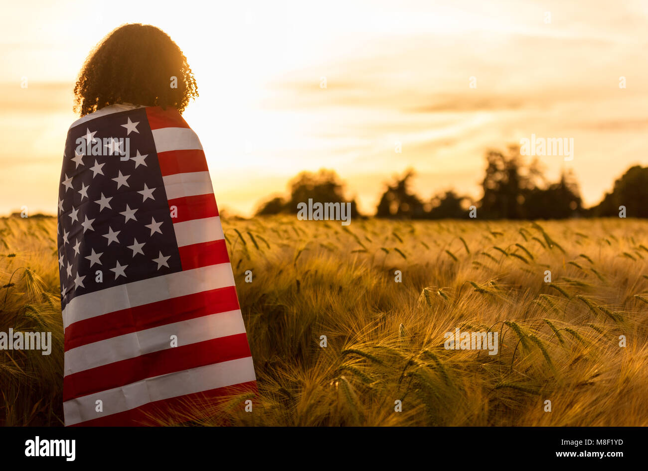 Mixed race African American girl teenager female young woman in a field of wheat or barley crops wrapped in USA Stock Photo