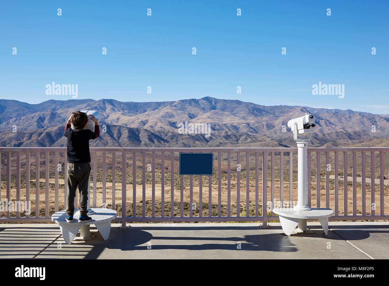 USA, Arizona, Boy (6-7) looking through coin operated binoculars - Stock Image