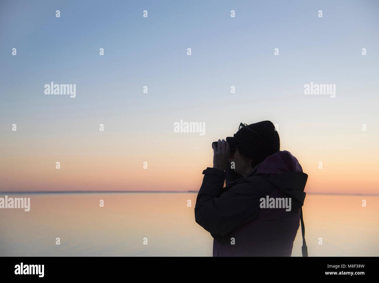Senior woman birdwatching at sunset - Stock Image