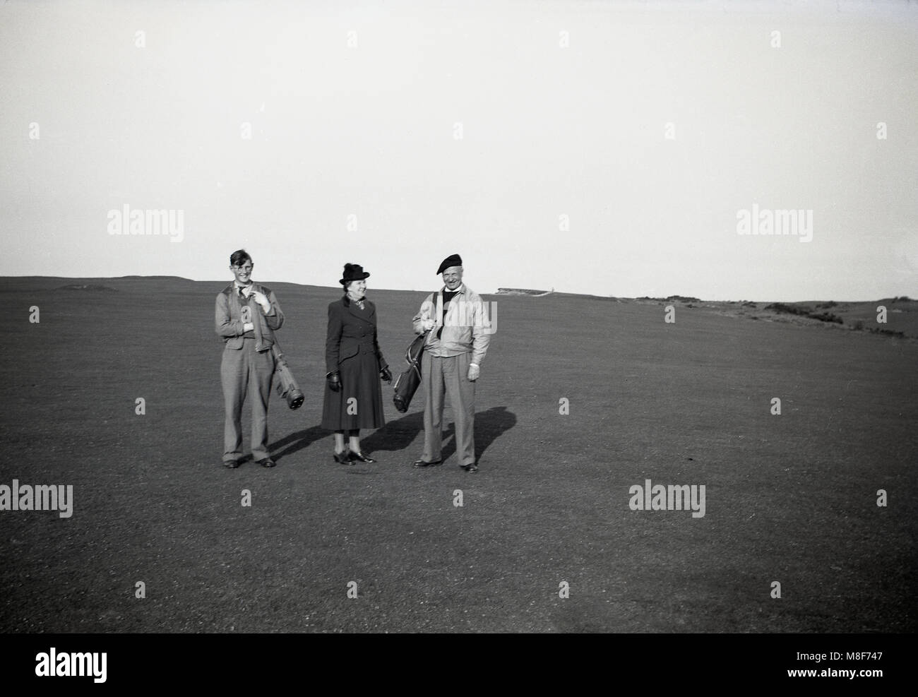 1930s, an eldlery male golfer with his wife and young adult golfer son standing together with their golf clubs on - Stock Image