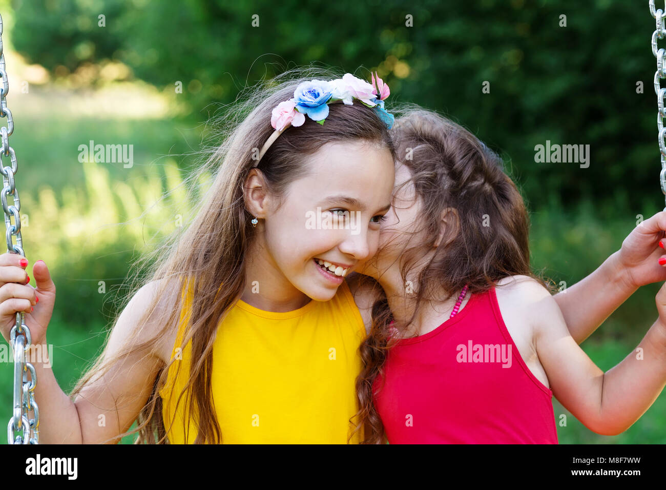 Two happy beautiful girls sitting on seesaw and talking at summer day - Stock Image