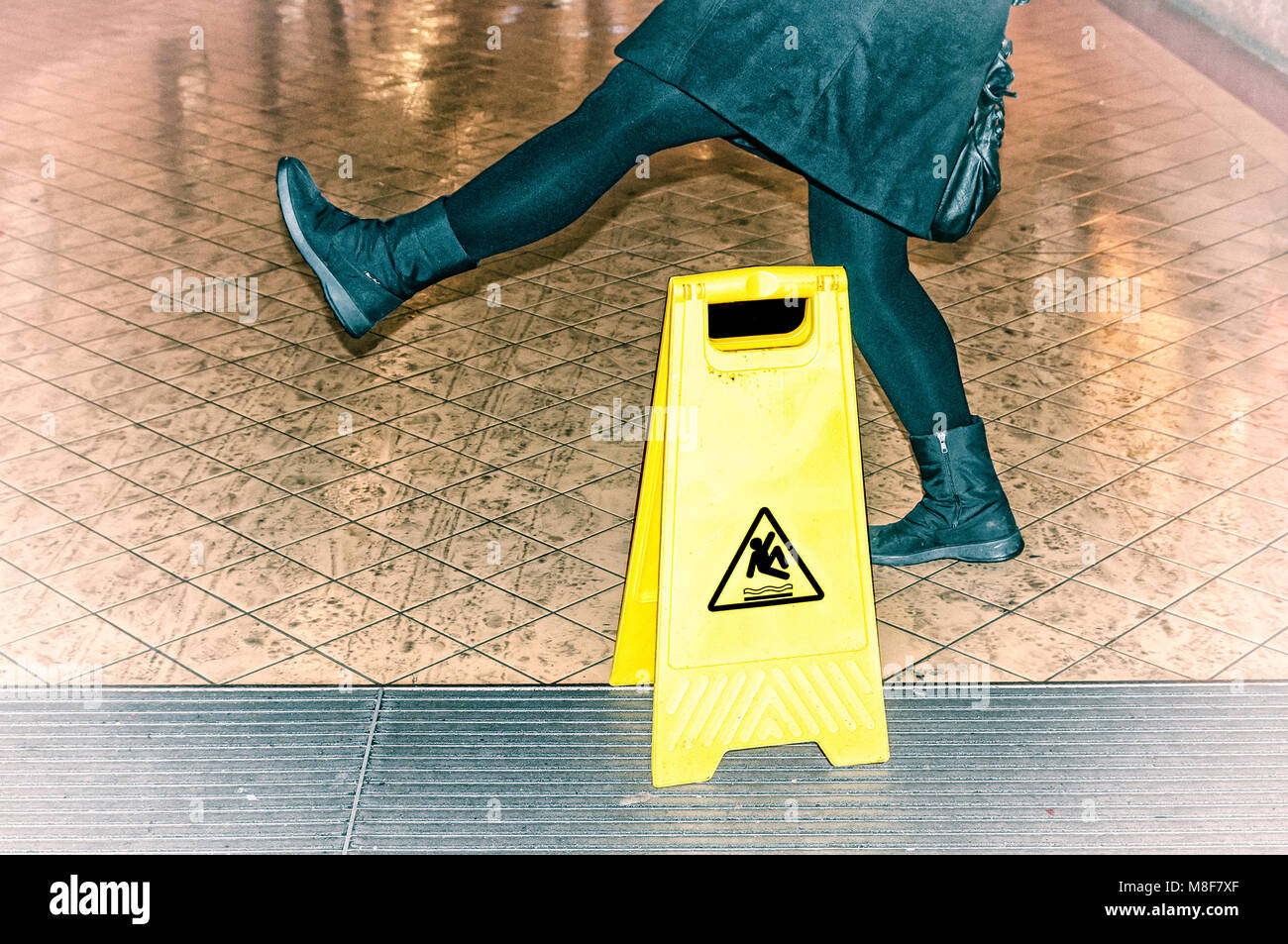 woman almost slips on a wet floor - Stock Image