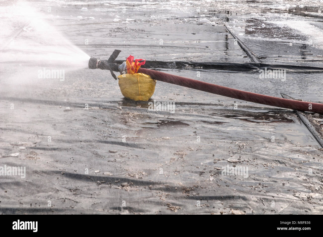 fire hose resting on a yellow bag sprays water spray over an ice rink - Stock Image