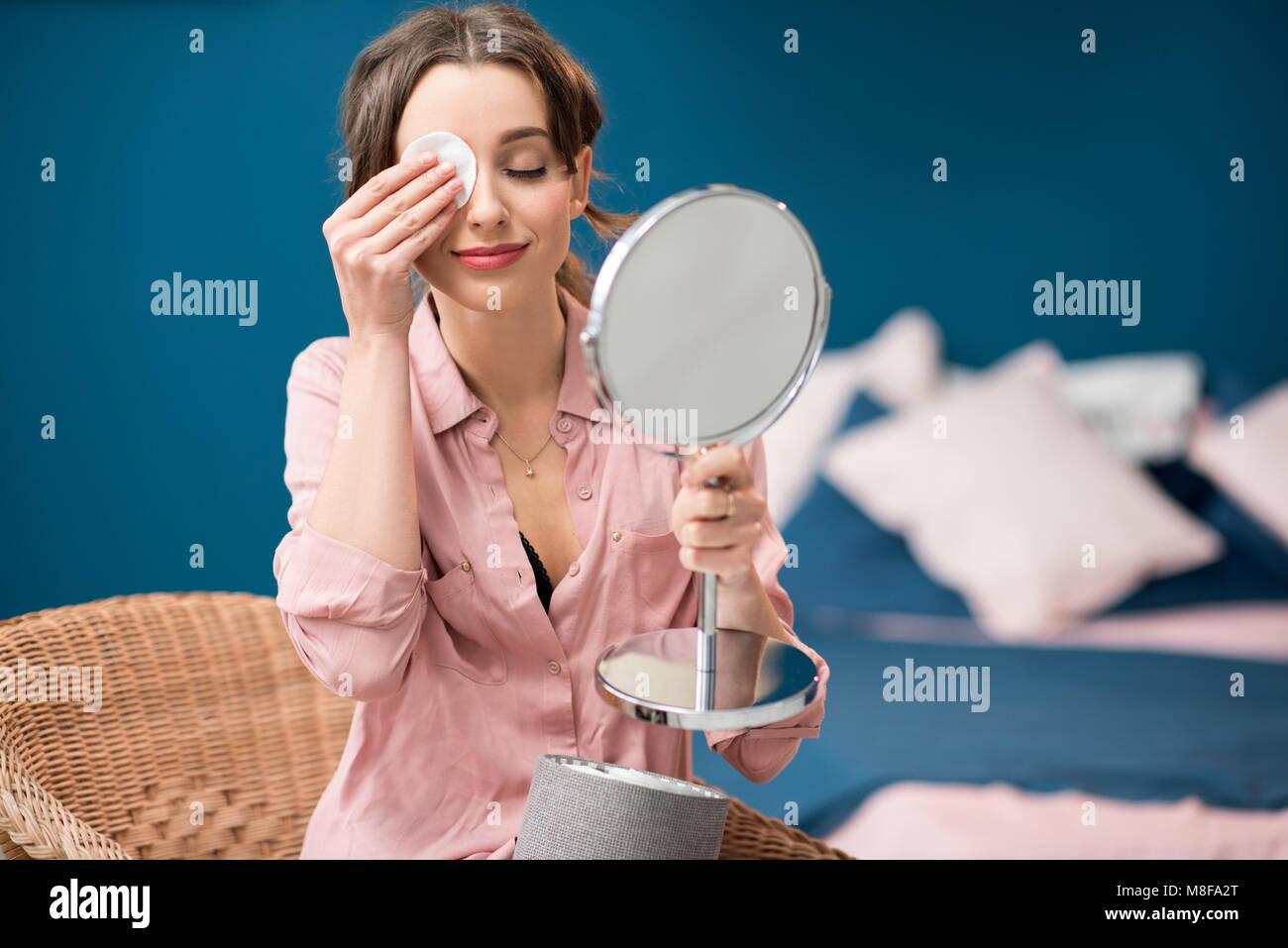 Woman using cotton swab indoors - Stock Image