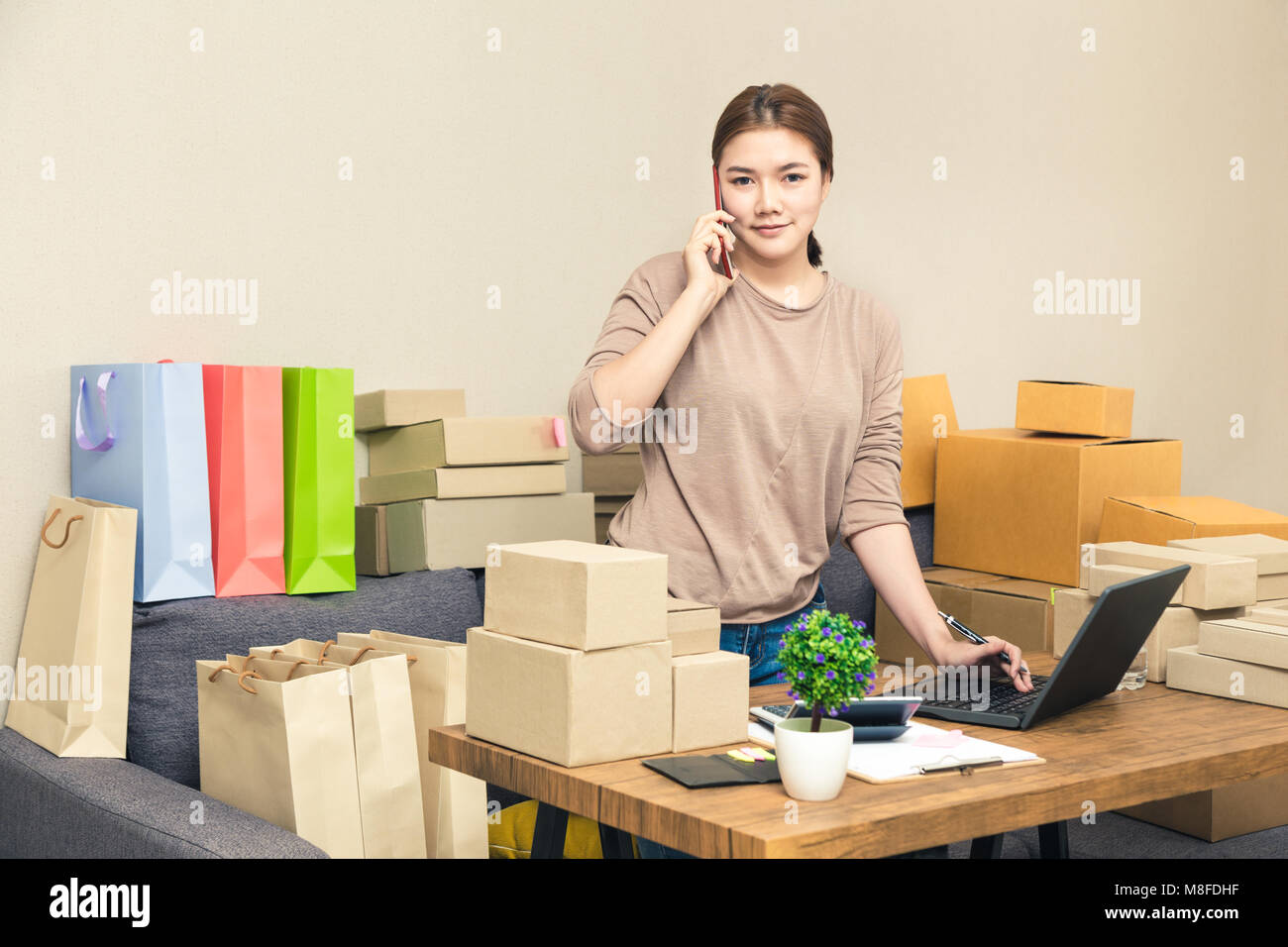Young happy asian online seller, business woman, in her home talking to her customer on her phone while looking Stock Photo