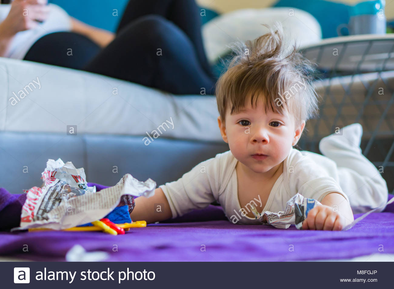 Baby boy lying on the floor and destroying a newspaper leaving pieces - Stock Image