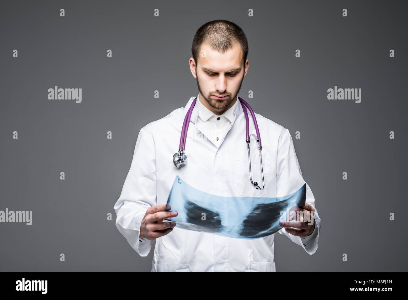 Attractive young male doctor looking to the camera seriously while examining an x-ray scan of his patient posing - Stock Image