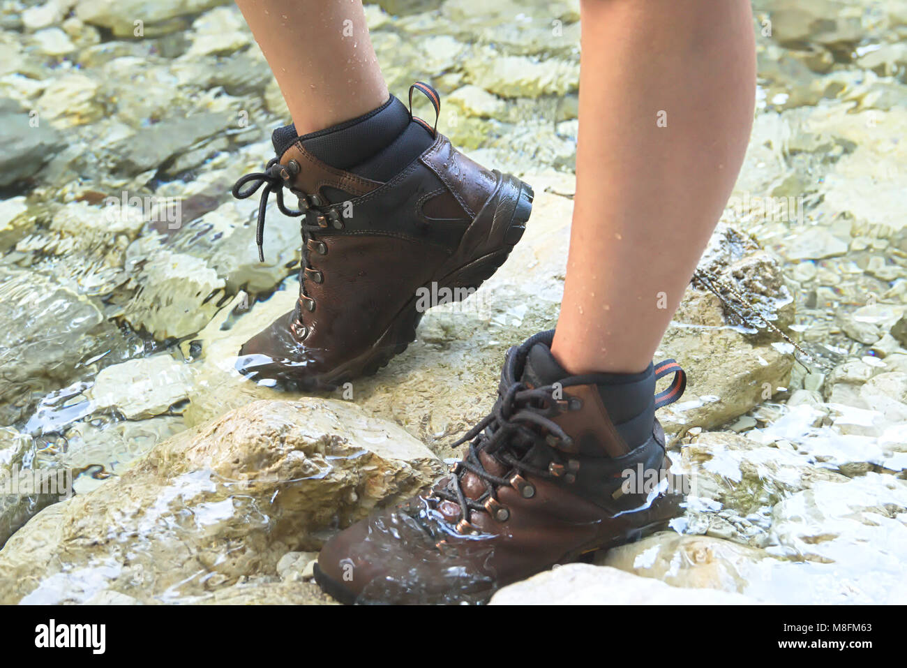 Young Woman Walking on the River with Hiking Boots - Stock Image
