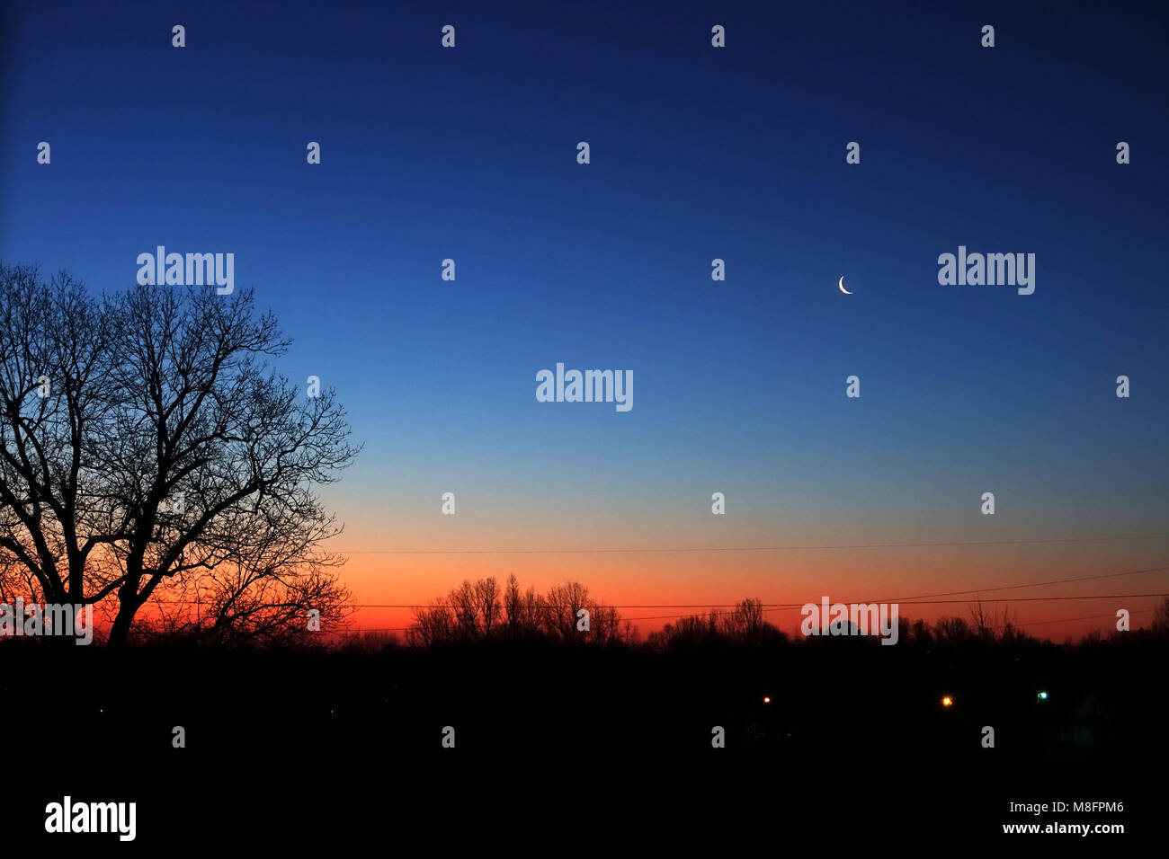 Break of day before sunrise with a crescent moon still visible. - Stock Image