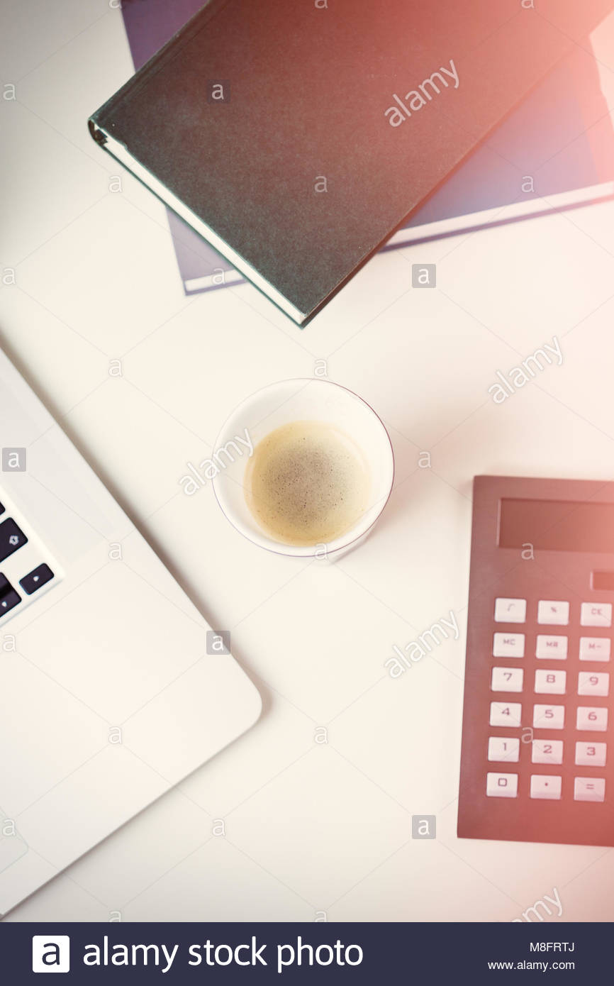 Neat desk or workstation viewed from above with an open laptop computer, calculator, cup of coffee and two journals - Stock Image