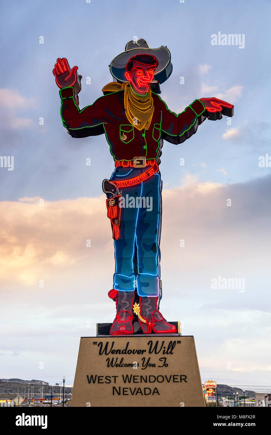 Neon figure of cowboy at sunset near casinos in West Wendover, Nevada, USA - Stock Image
