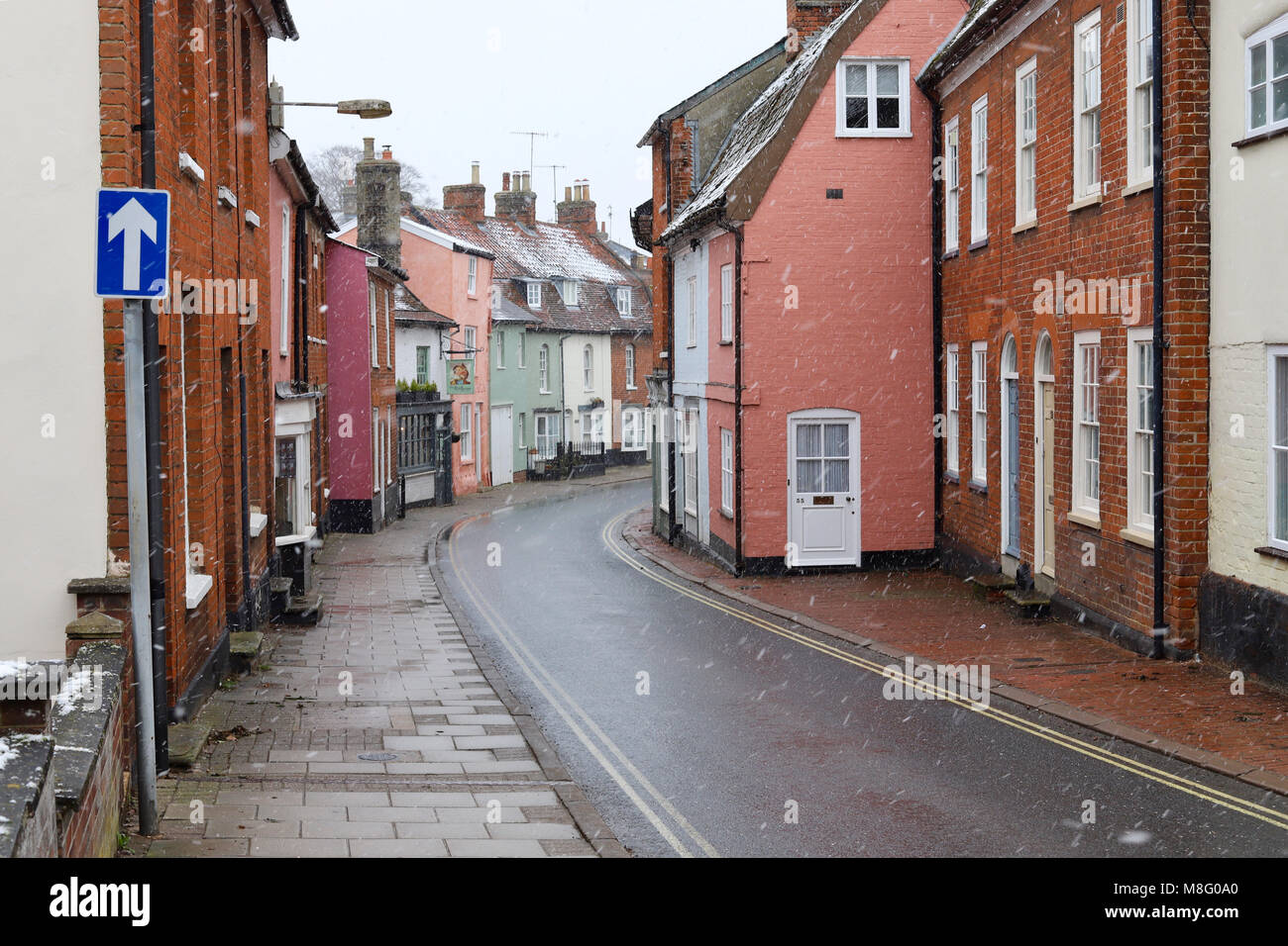 One way narrow street of colourful buildings in Woodbridge, Suffolk. Winter, light snow, March 2018. - Stock Image