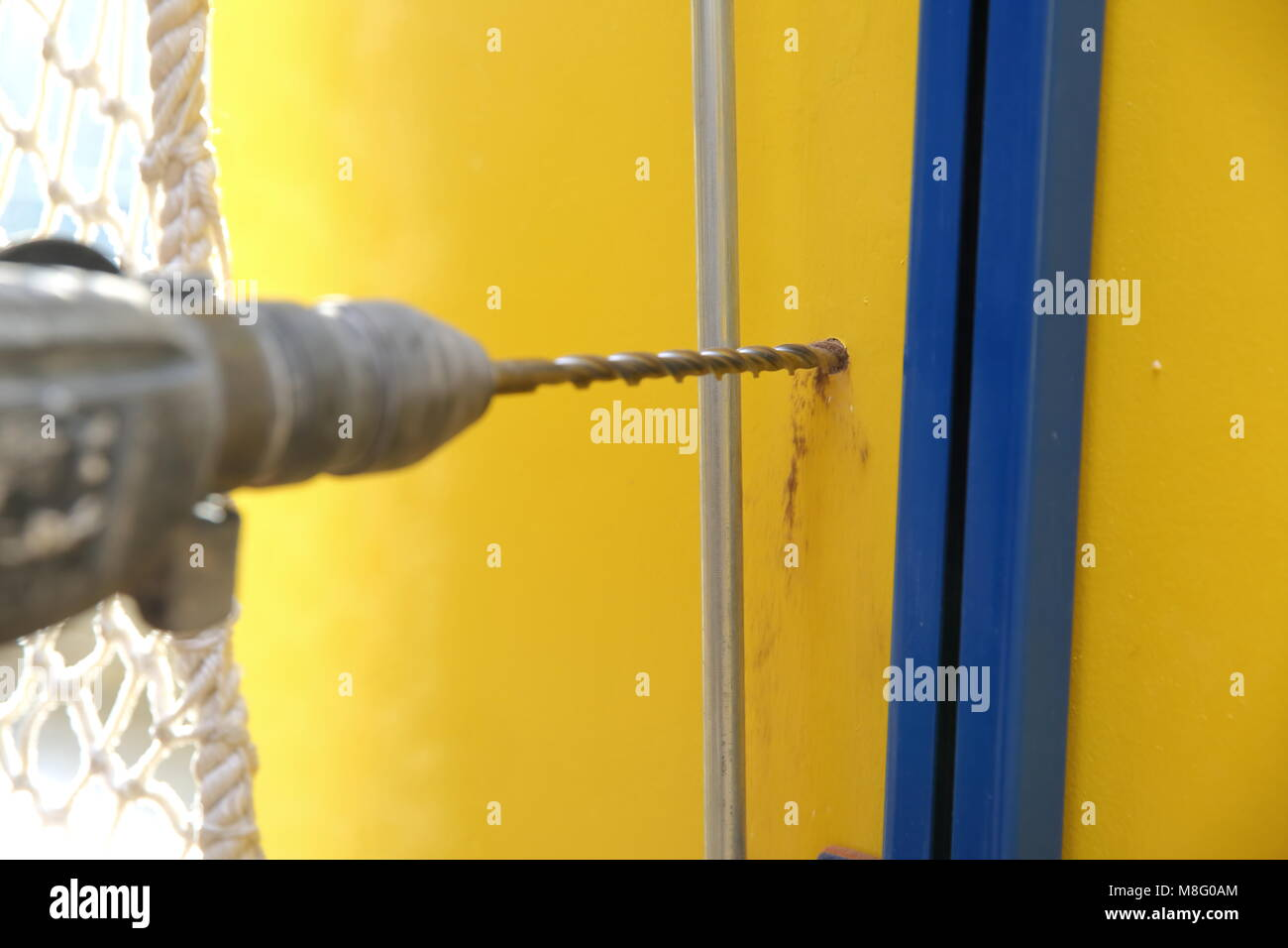 During drilling with a hammer drill, a lot of shocks and large noise are generated if the wall is solid concrete. Stock Photo