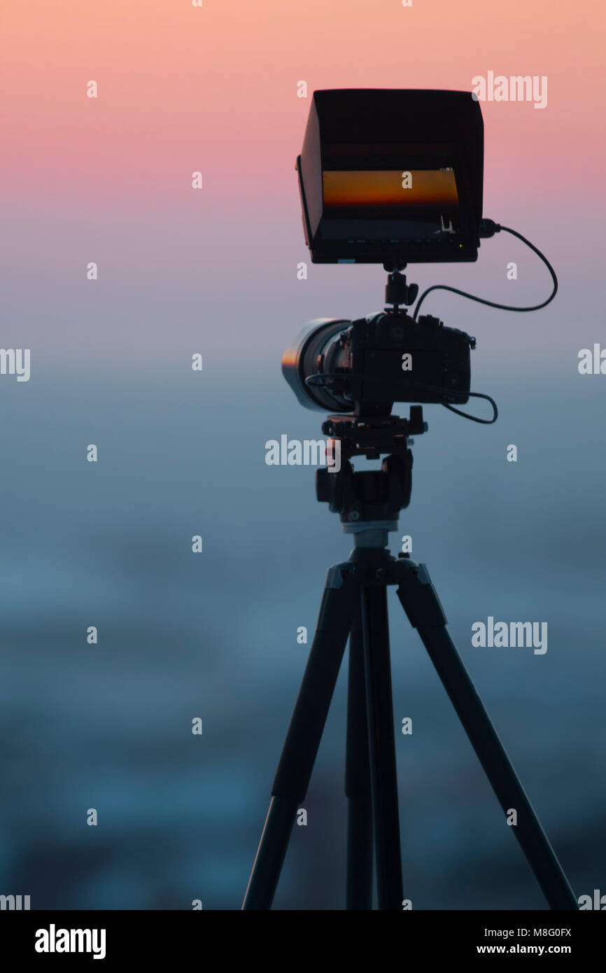 View of camera on tripod shooting beautiful winter landscape - Stock Image