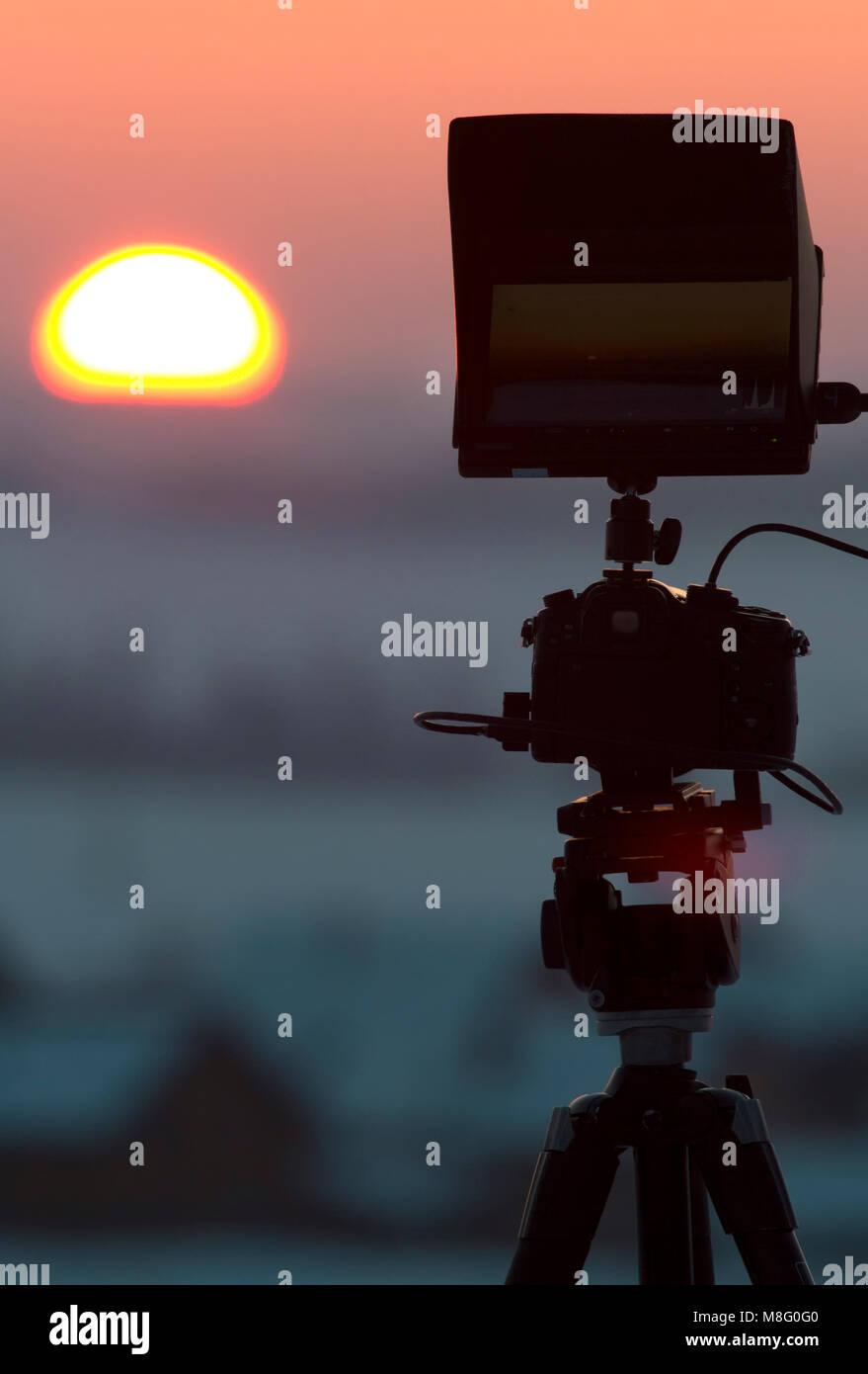 Silhouette of camera on tripod shooting beautiful winter sunrise - Stock Image