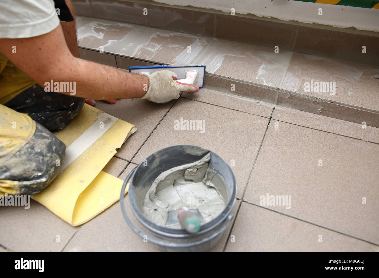 This manual hard work is necessary to finish and achieve the final visual effect of laying terracotta tiles from - Stock Image