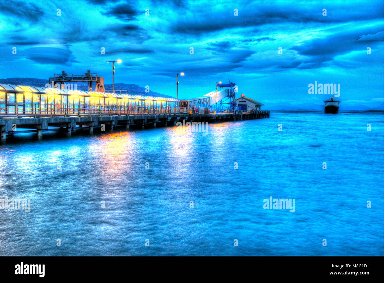 Isle of Mull, Scotland. Artistic dusk of the Oban to Craignure Cal Mac ferry arriving at Craignure Harbour. - Stock Image