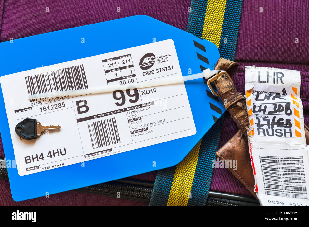 labels on lost suitcase being sent on following flight for home delivery from Singapore to Heathrow via Singapore - Stock Image