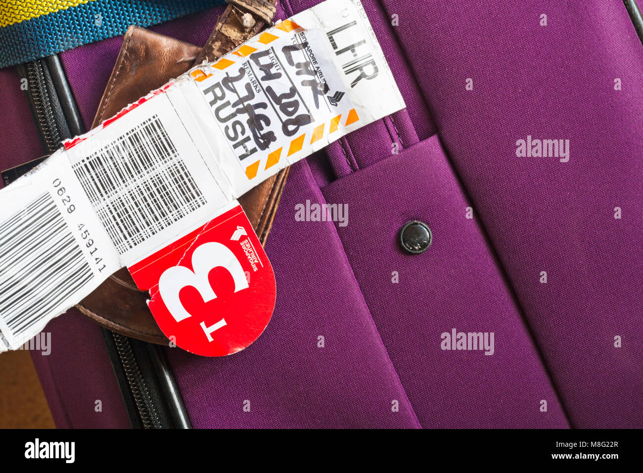 label on lost suitcase being sent on following flight for home delivery from Singapore to Heathrow via Singapore - Stock Image