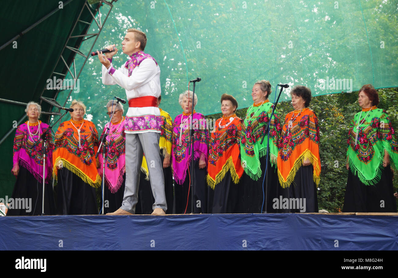 Mstyora,Russia-August 16,2014: Young person on scene sings with in chorus from elderly womans - Stock Image