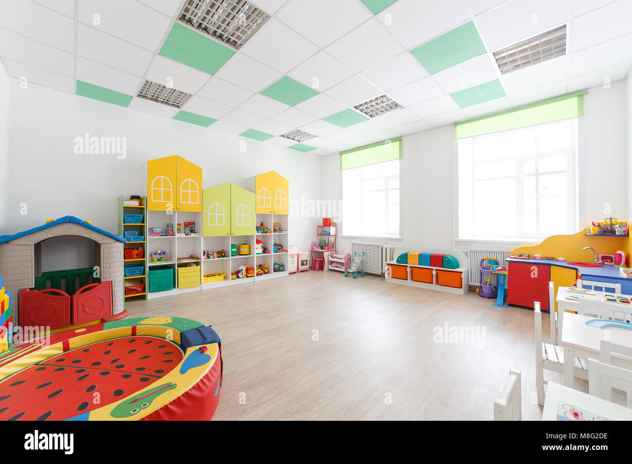 Spacious white game room in the kindergarten with toys, two large windows and tables for classes. - Stock Image