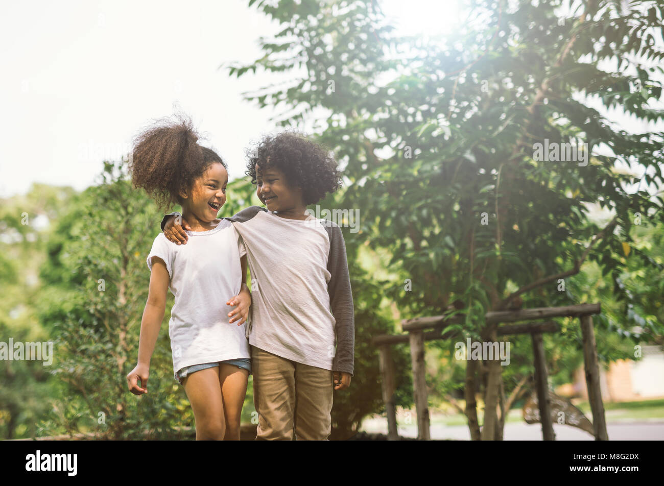Children Friendship Togetherness Smiling Happiness Concept.Cute african american little boy and girl hug each other - Stock Image