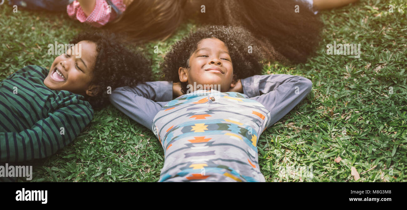 happy children kids laying on grass in park - Stock Image