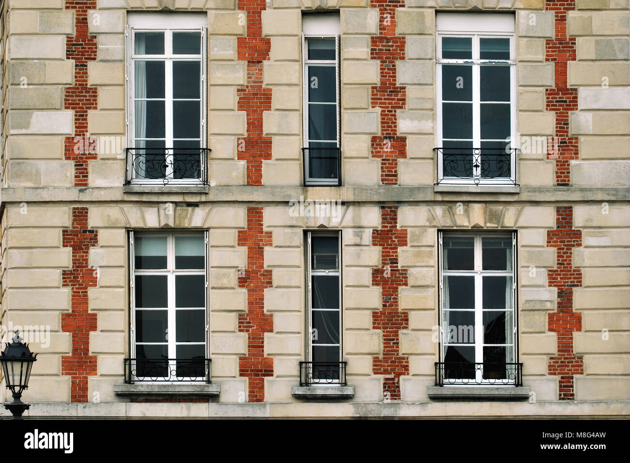 Paris windows against a background of beige walls with red brick spacers and balconies with iron bars. - Stock Image