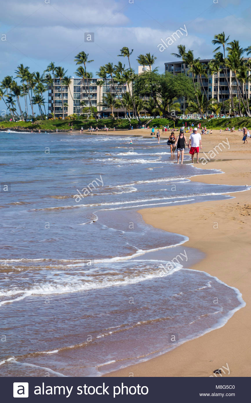 Gentle surf and people walking the beach at Kamaole Beach Park 11 in Kihei island of Maui in the state of Hawaii - Stock Image