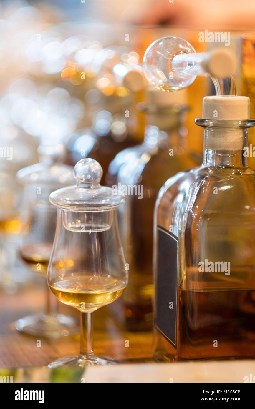 Whiskey or whisky tasting: Bottles with glasses - the jars are still covered in order to preserve the aroma - are - Stock Image