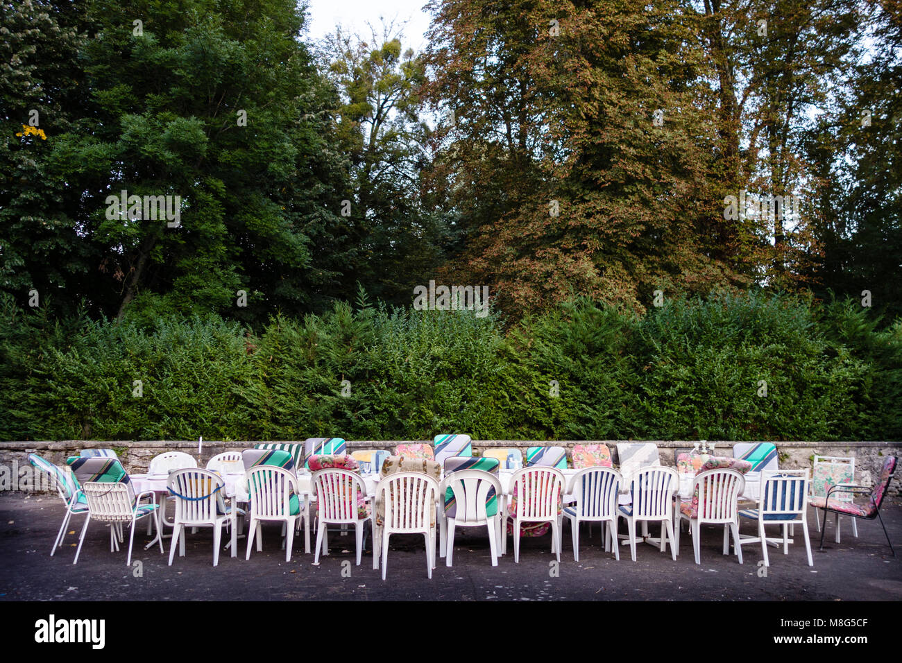 Long table and chairs with mixed upholstery outside on the courtyard waiting for a group of friends on holidays - Stock Image