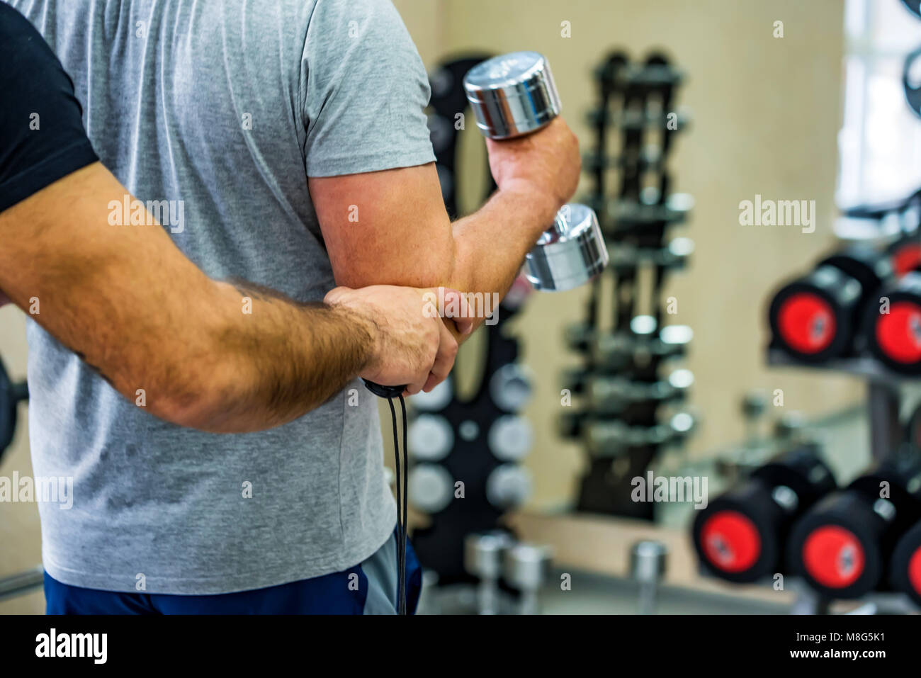 Back view man trains biceps with trainer in gym - Stock Image
